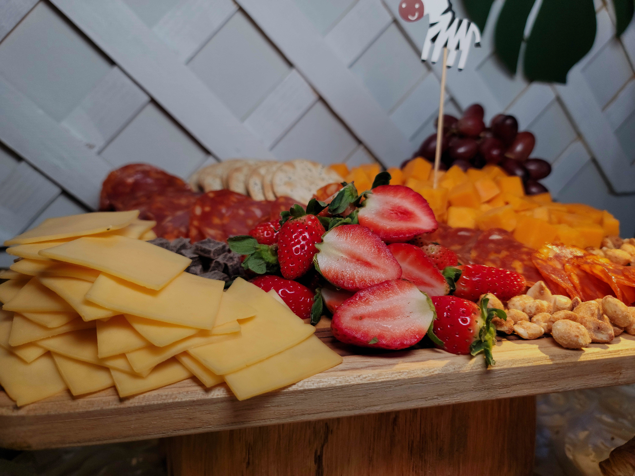 A catering table with a cheese platter and some fruits decorated with a foam zebra