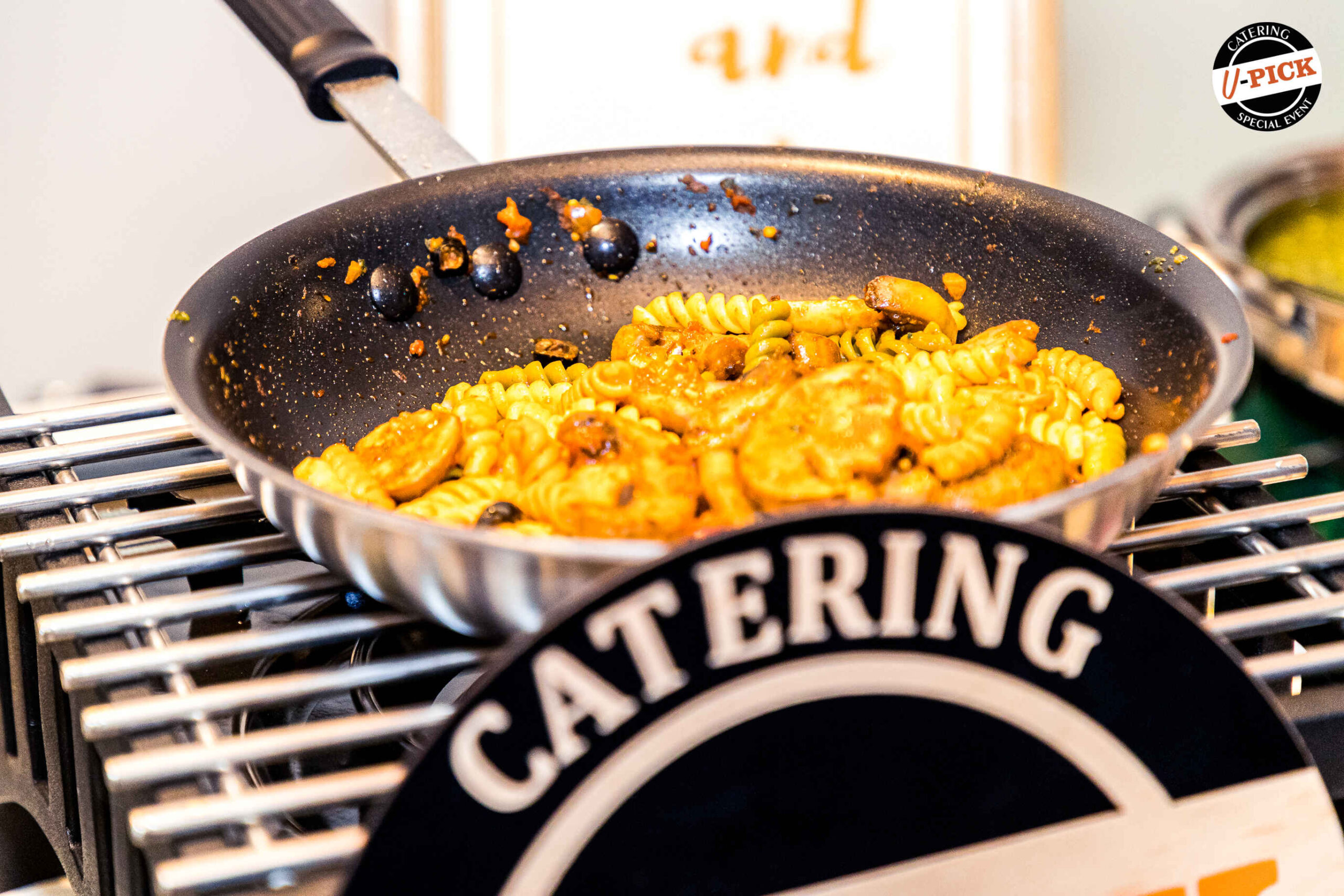 Frying pan with pasta and a catering sign in front