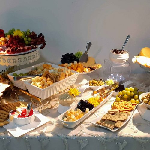 Table with a decorated white tablecloth showing Upick's catering service with different fruits, snacks and appetizers