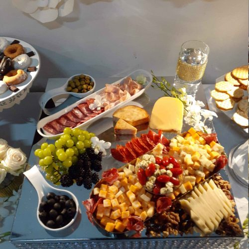 Food placed elegantly in a white table with various cheeses