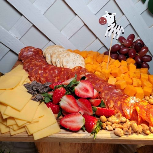Upper view of a catering table with a cheese platter and some fruits decorated with a foam zebra
