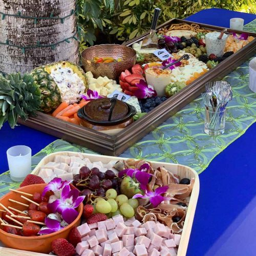 Table with blue decorated tablecloth with a tray of appetizers on top with different fruits, vegetables and delicatessen