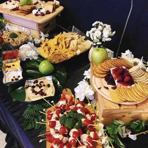 Black table with fruits and different snacks on top