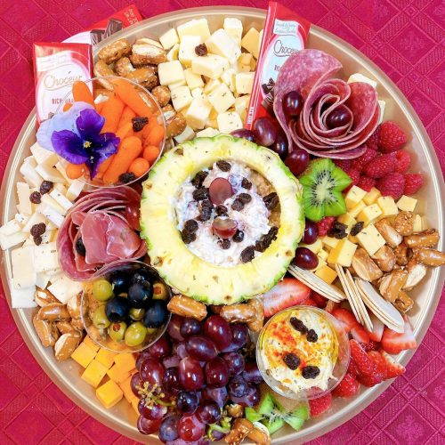 upper view of a catering table with a red tablecloth some fruits