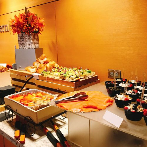 Event in a wood-finished venue with a white ceramic countertop showing different meals from a catering service